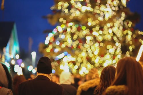 Unrecognizable people enjoying Christmas tree with lights on street