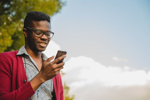 Positive African American male in eyeglasses text messaging on cellphone while standing against cloudy sky and green tree on street
