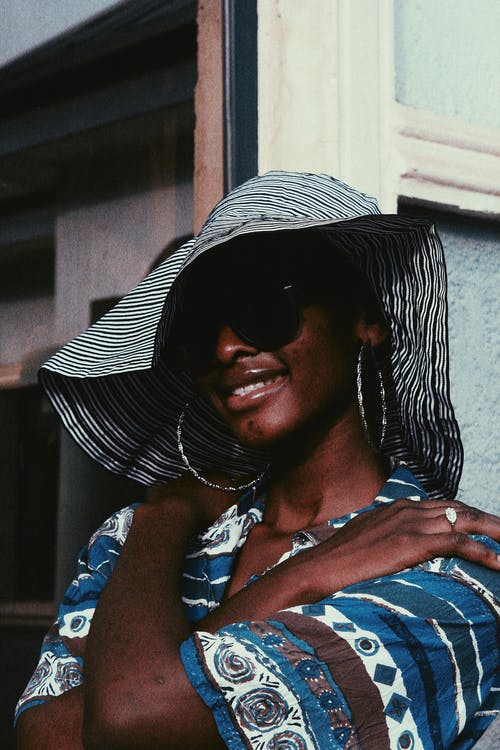 Stylish black female in hat standing with crossed arms
