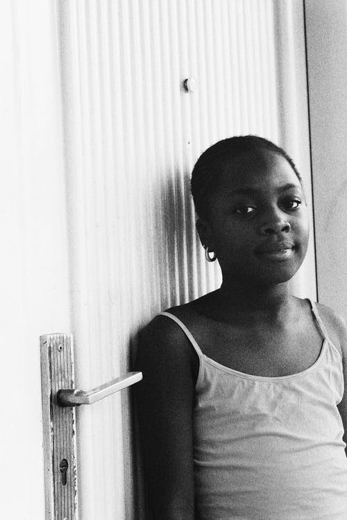 Young black girl leaning on door and looking at camera