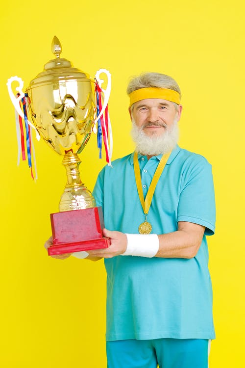 Man in Blue Scrub Suit Holding Trophy
