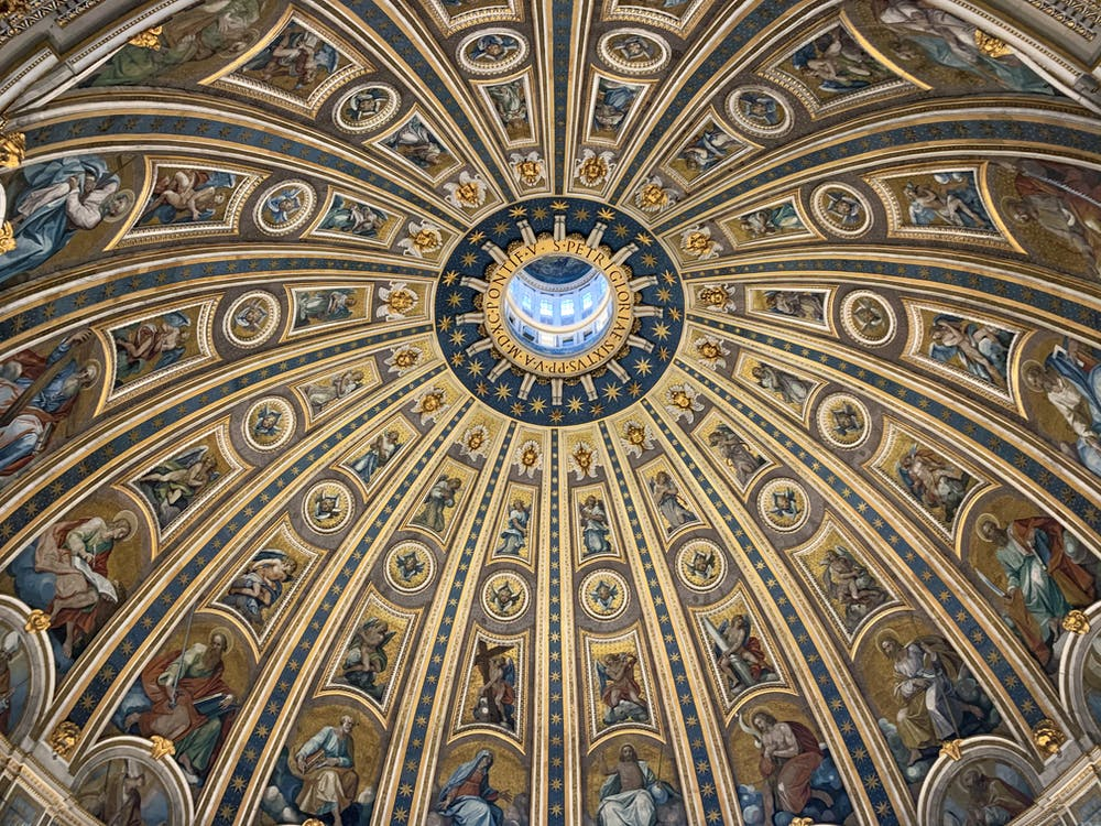 From below amazing dome ceiling with ornamental fresco paintings and stucco elements in St Peters Basilica in Rome
