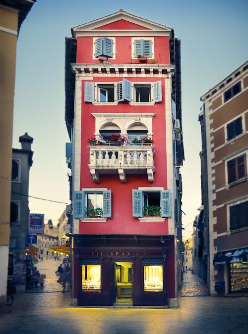Asfalt yol, balkon, camlar, eski bina içeren Ücretsiz stok fotoğraf