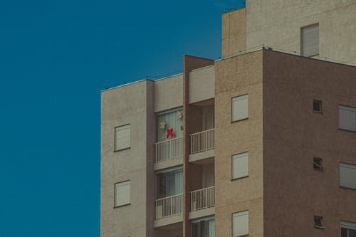 Low angle of concrete building with balconies with star and ribbon shaped decorations on window in residential district