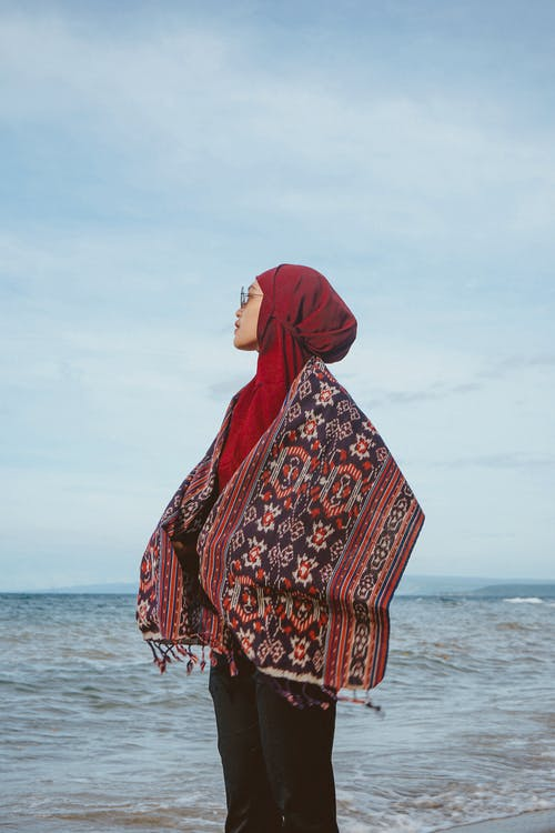 Ethnic woman in traditional scarf standing on beach in solitude
