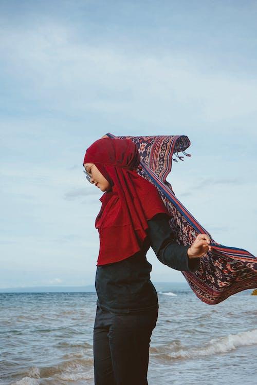 Ethnic woman putting on scarf on beach