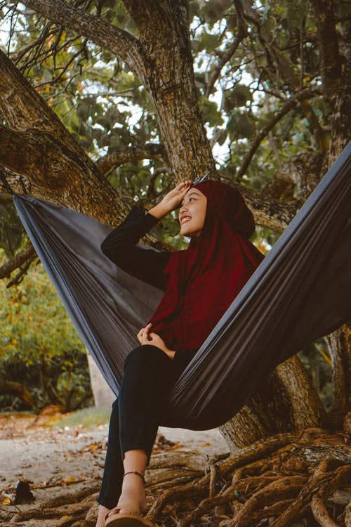 From below of smiling Muslim woman sitting in hammock with crossed legs during trip in exotic country