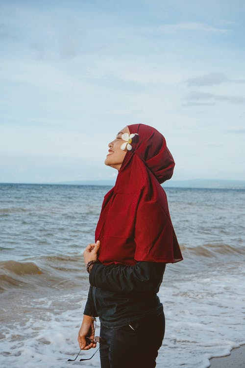 Side view of smiling Muslim female standing on beach washed by waving foaming sea during vacation