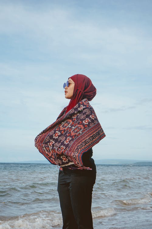 Low angle side view of tranquil Muslim woman wrapped in scarf enjoying solitude near waving sea