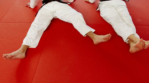Person in White Pants Lying on Red Carpet