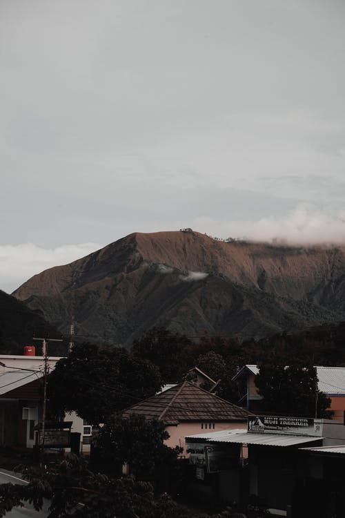 Residential buildings located in village among mountain range in highland covered with thick clouds