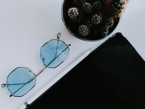 Sunglasses near modern tablet on table
