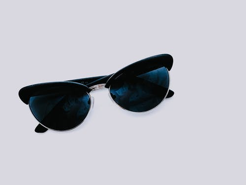 From above of trendy sunglasses with dark lenses and creative design placed on clear white background in modern light studio