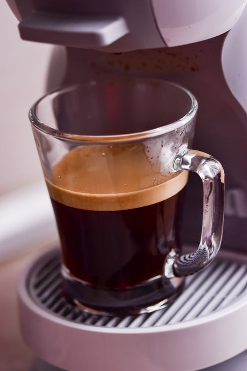 Cup with coffee in coffee machine