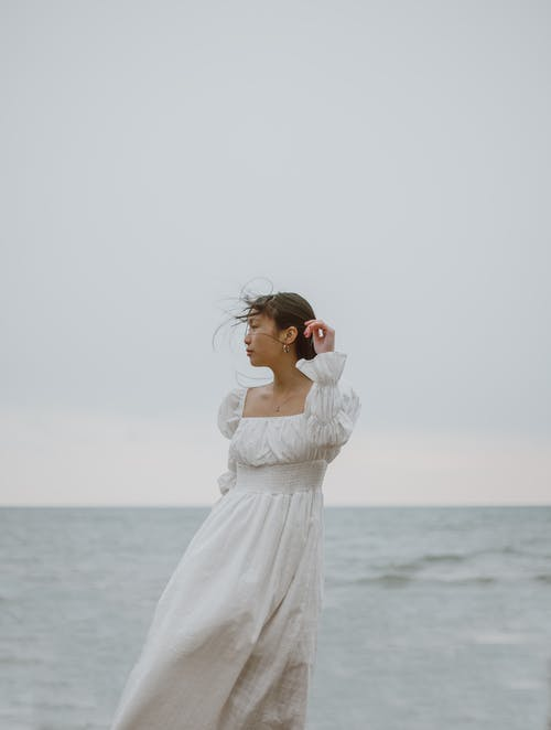 Gentle Asian traveler in white dress contemplating sea