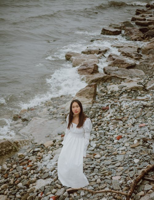 From above of gentle ethnic female tourist in white dress looking at camera from pebble ocean shore