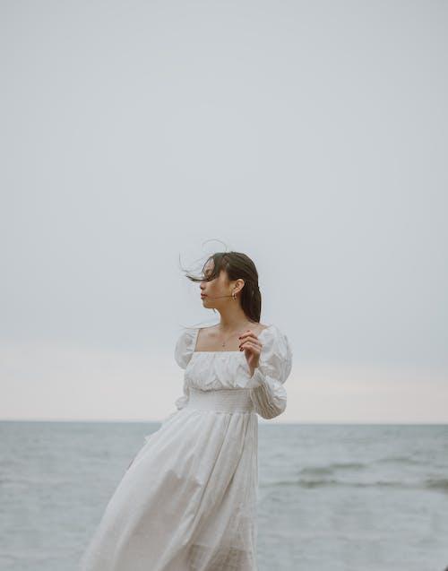 Mulher Com Vestido Branco De Manga Comprida Em Pé Na Praia