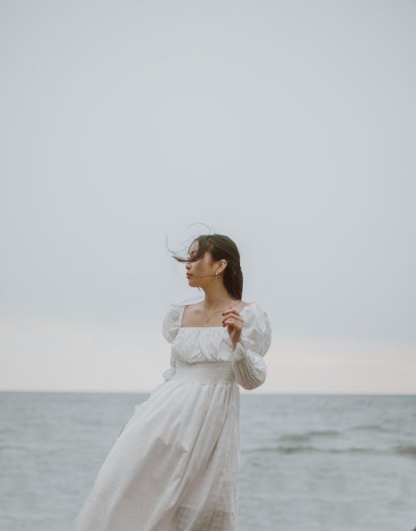 站在海邊的白色長袖連衣裙的女人