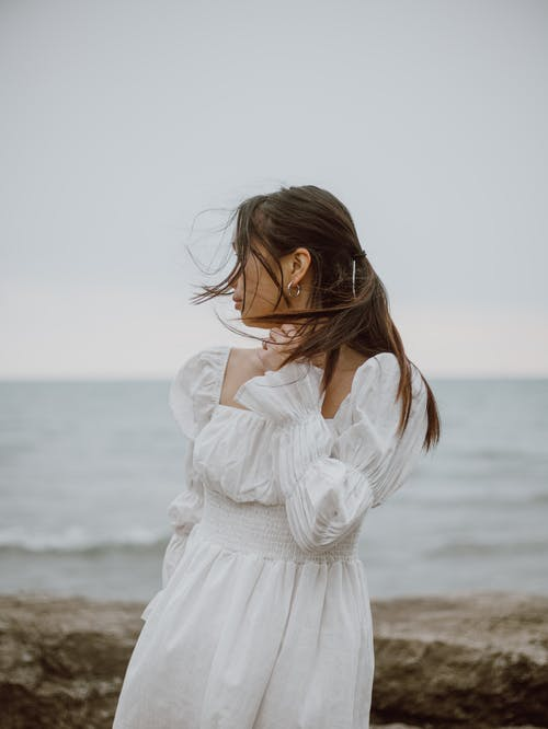 Young contemplative female traveler in dress touching neck while looking away from coast against ocean