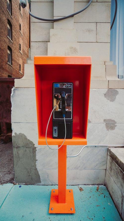 Payphone near shabby wall on street