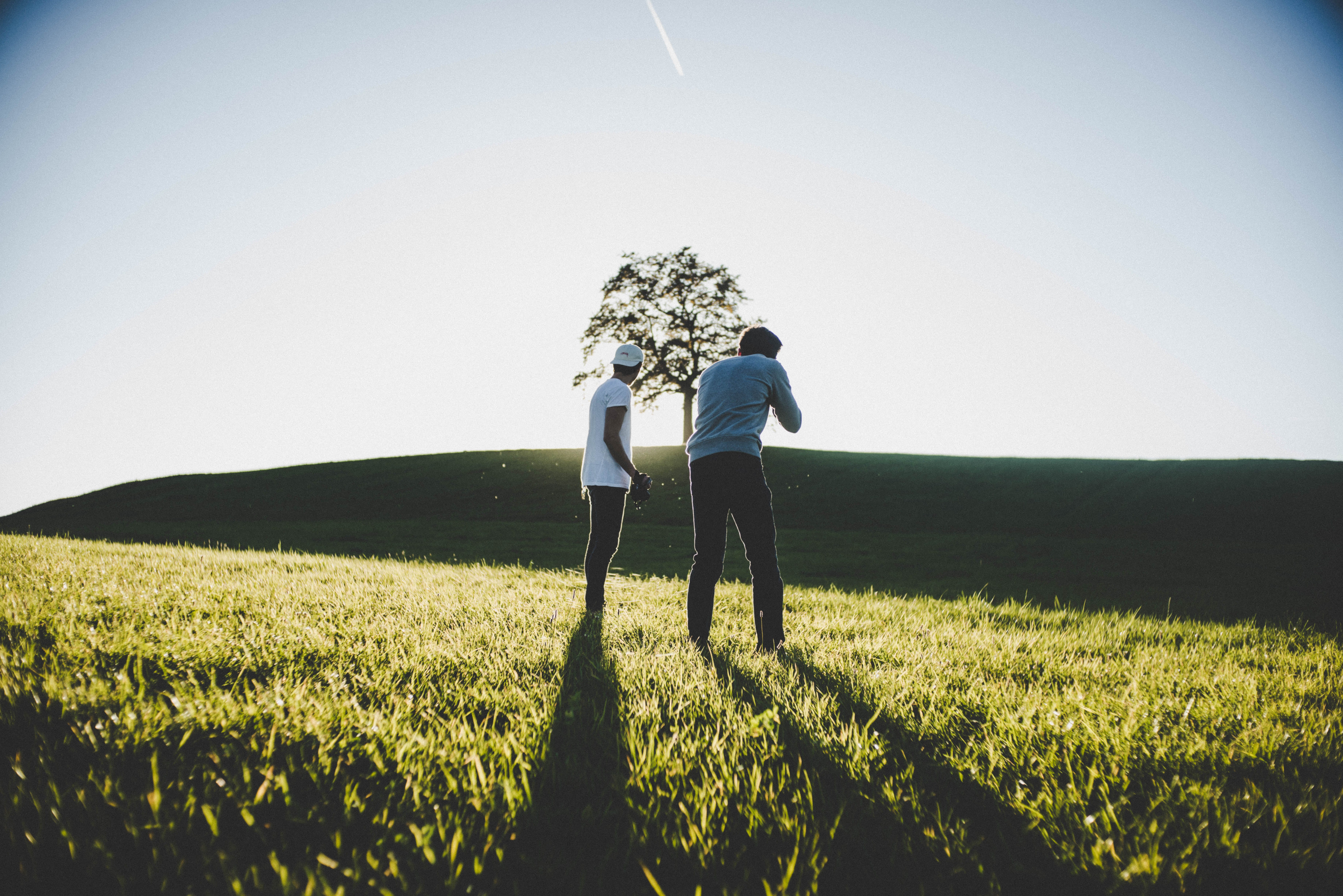 Two Men Standing on Green Grass