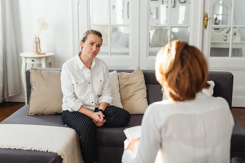 Woman in White Long Sleeves Sitting on Gray Sofa Talking to Person in White Long Sleeves Top
