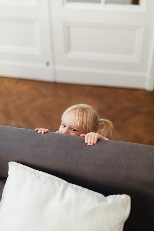 Foto profissional grátis de criança, dentro de casa, escondendo