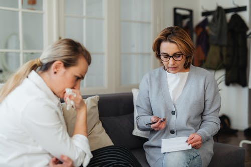 Woman in Gray Long Sleeves Sitting beside Woman in White Long Sleeves
