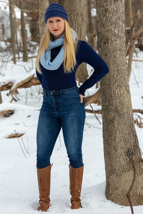 Woman in Blue Long Sleeve Shirt and Blue Denim Jeans Standing on Snow Covered Ground