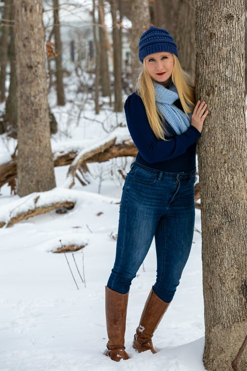 Woman in Blue Denim Jeans Standing on Snow Covered Ground
