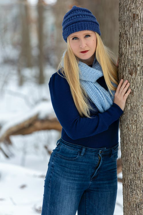 Woman in Blue Long Sleeve Shirt Leaning on Brown Tree Trunk