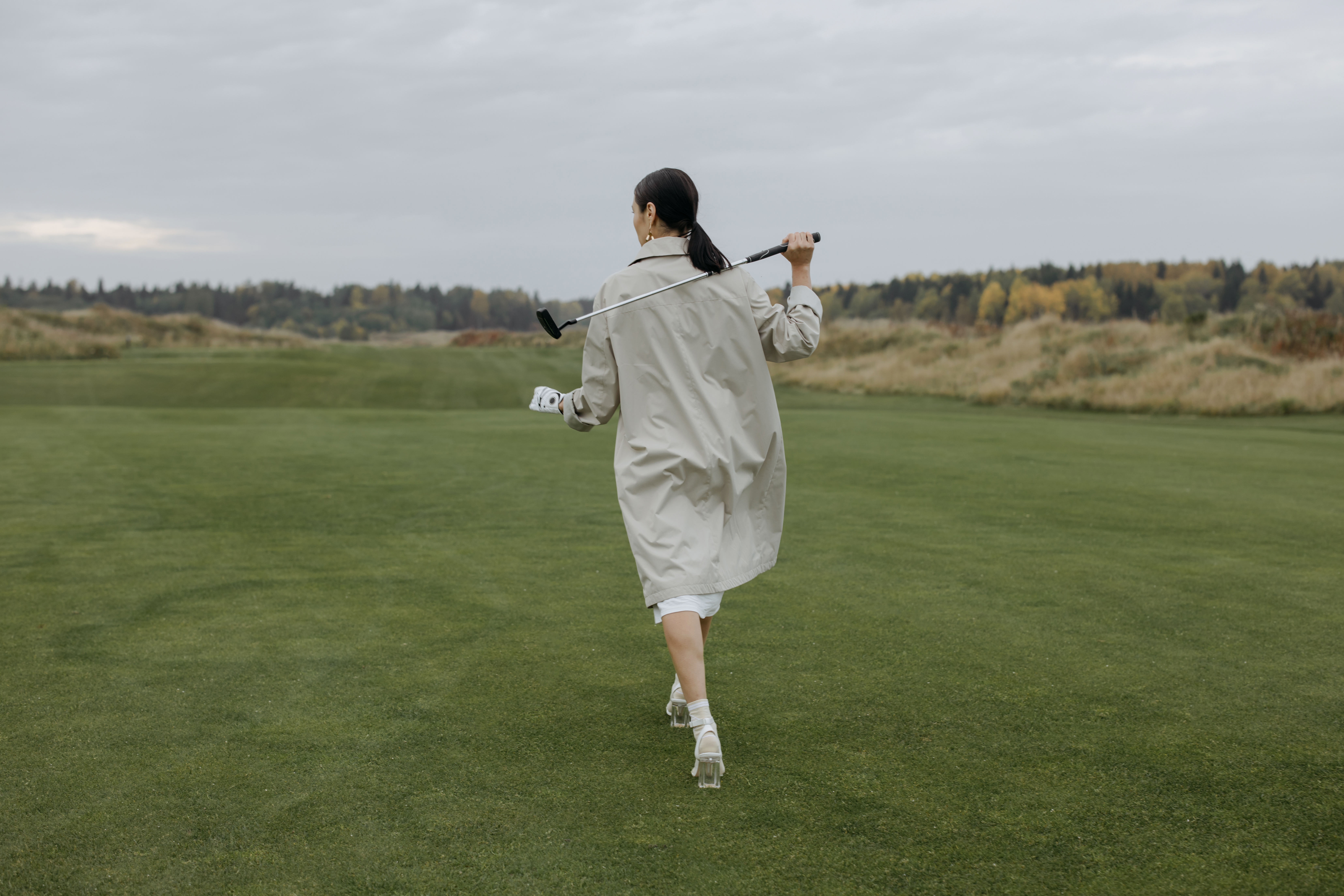 man in white dress shirt and white shorts standing on green grass field