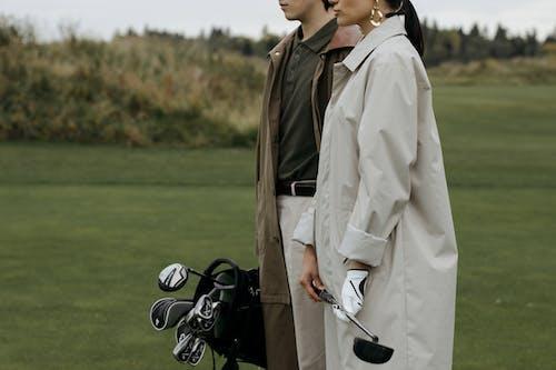 Man In Bruine Jas Met Zwarte En Zilveren Golfclub