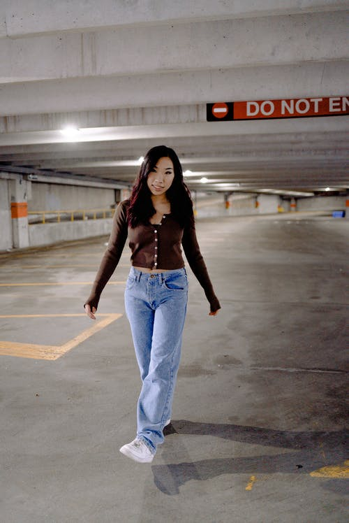 Woman in Black Jacket and Blue Denim Jeans Standing on Gray Concrete Floor