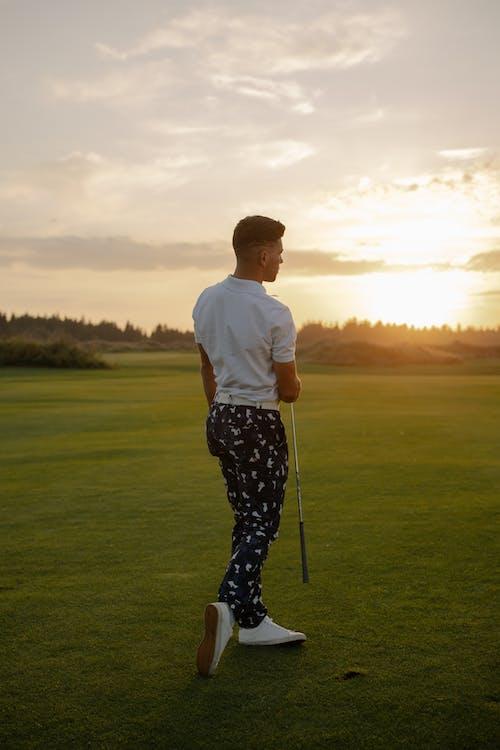 Man In Wit T Shirt En Zwart Wit Geruite Broek Golfen