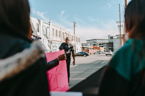 Woman in Black Shirt and Black Pants Standing on Sidewalk