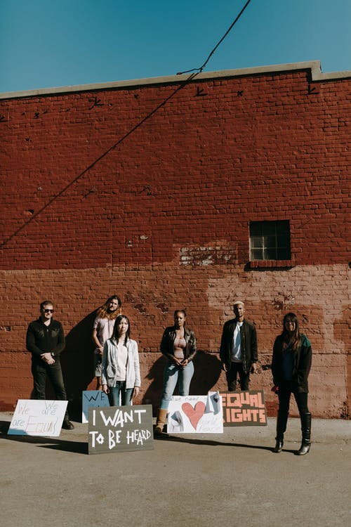 Group of People Standing Near Brown Brick Wall