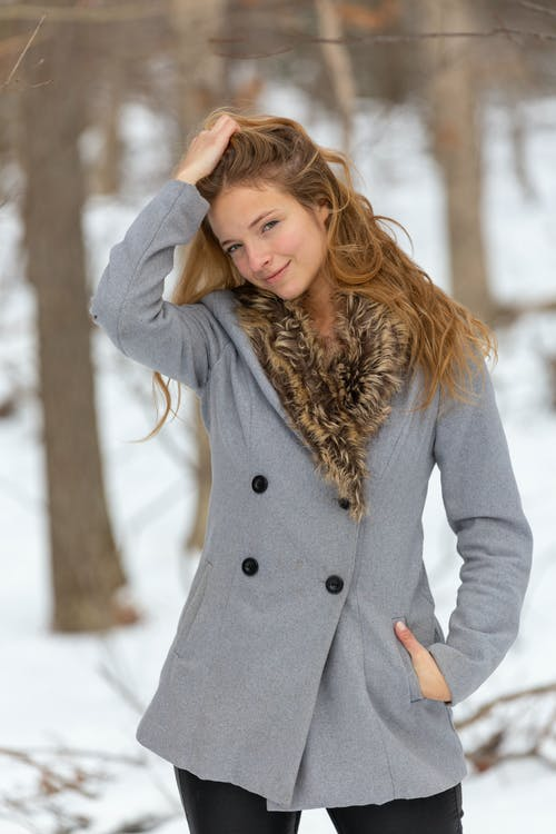 Woman in Gray Coat Standing on Snow Covered Ground