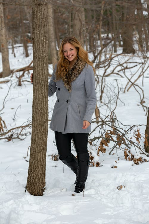 Full body of smiling female in stylish coat touching tree trunk while standing on snowy ground in forest with branches