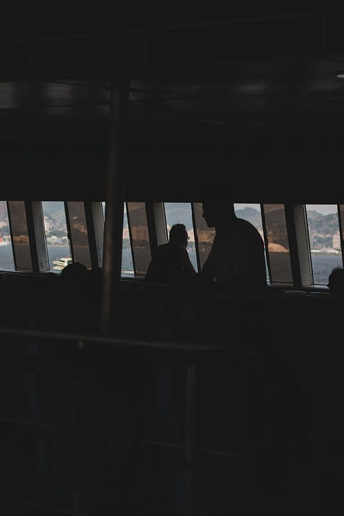 Silhouettes of unrecognizable passengers inside power boat travelling on river in sunny day