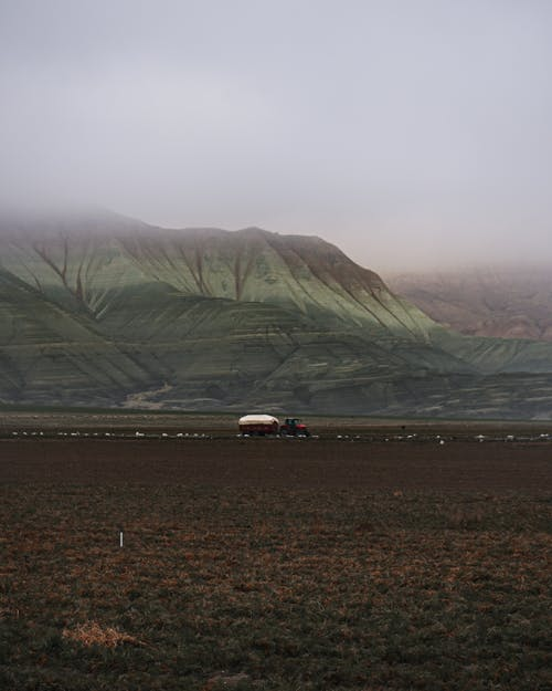 Tractor Below a Mountain