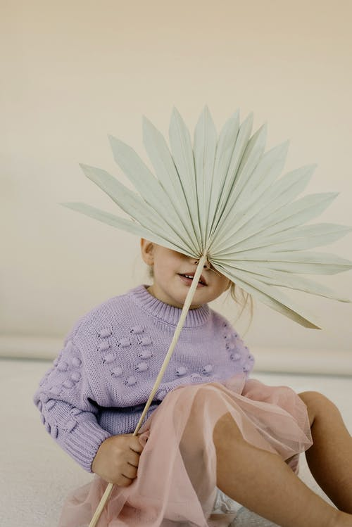 Child Holding an Origami Fan