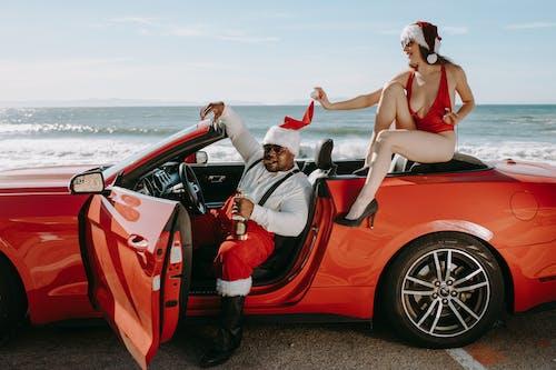 Uomo E Donna In Abiti Da Babbo Natale Seduto In Una Macchina Decappottabile Rossa