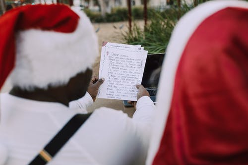 Man In Red Santa Outfit Reading A Message On Paper