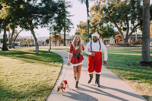 Man And Woman In Santa Outfit Walking On Concrete Pathway With A Dog