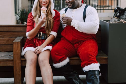 Cropped Photo Of Man And Woman In Santa Outfits Eating Ice Cream