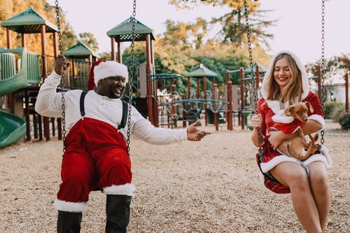 Man And Woman In Santa Outfit Sitting on Swing