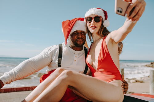 Man And Woman In Santa Outfits Taking Selfie