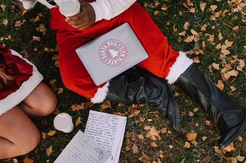 Two People In Santa Outfit Sitting On Grass With Drinks