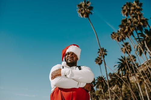 Man in Santa Outfit Standing Under Blue Sky